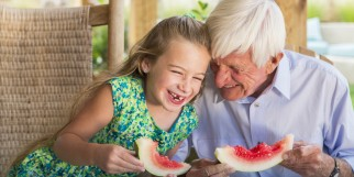Caucasian man and granddaughter eating watermelon